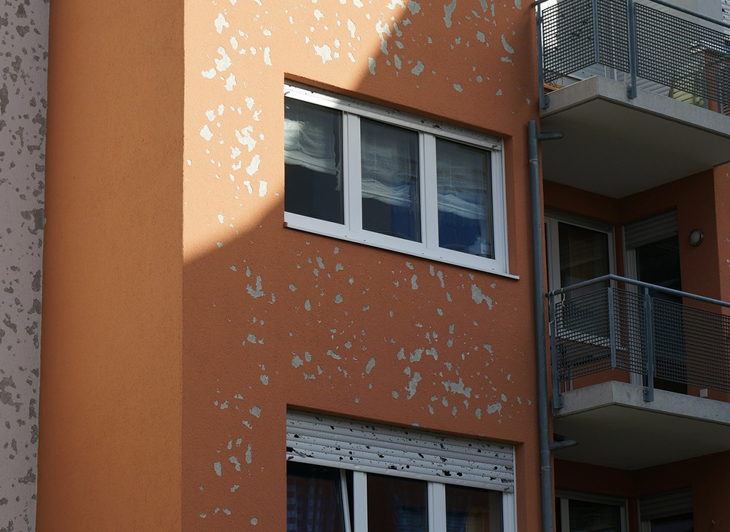 The figure shows damage to a house facade caused by hail.
